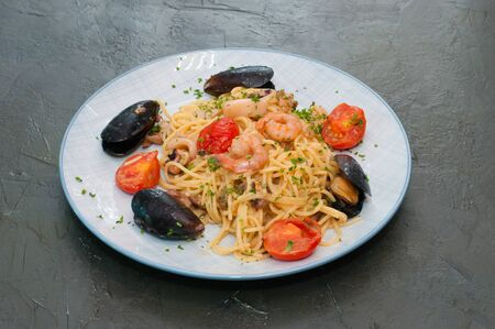 Spaghetti pasta with shrimp mussels, tomatoes and cheese. Standard-Bild - 131686992