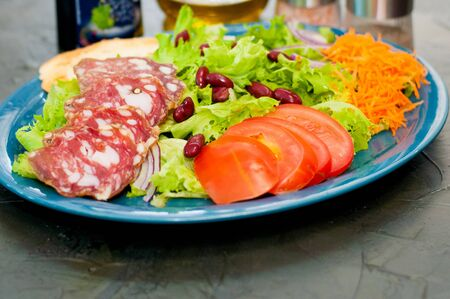 Salad with sausage, tomatoes, beans carrots, spices, olive oil or sauce. Restaurant serving Italian food Standard-Bild - 131691912