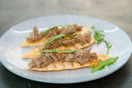Toasts with pate and arugula. Festive appetizer New Years Italian dish. The view from the side and there is room for text