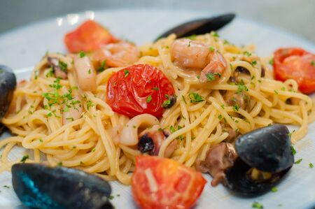 Spaghetti pasta with shrimp, mussels, tomatoes and cheese, close-up, side view. Tasty, traditional food of Italians Фото со стока - 134084489