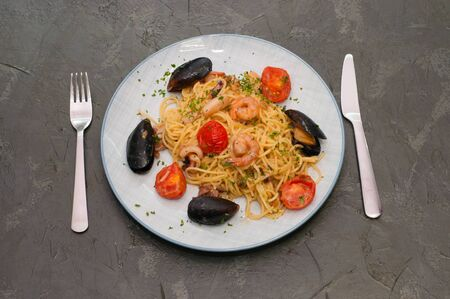 Spaghetti pasta with shrimp, mussels, tomatoes and cheese. Tasty traditional Italian food Фото со стока - 134084558
