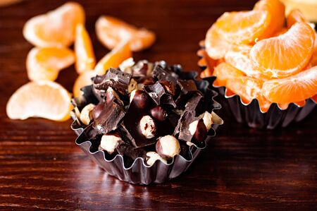Chocolate with nuts and mandarin slices close-up top view and side view