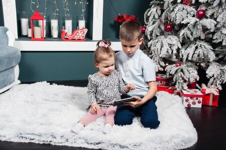 Cute kids, boy and girl, sister and brother are sitting near the Christmas tree and fireplace and watching cartoons on a smart phone
