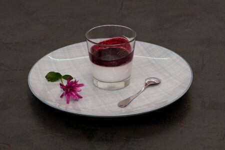 Italian festive dessert Panacota with berry filling in a glass