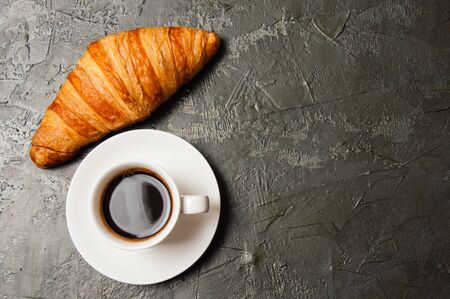 Coffee in white cup and a croissant on a dark concrete background, top view, flat lay. Concept for breakfast, coffee break or business lunch. There is a place for text on the right