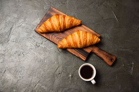 Strong espresso or ristretto coffee in a white cup and two tasty croissants on a dark concrete background, on a wooden board, flat lay. Concept for breakfast, coffee break or business lunch.
