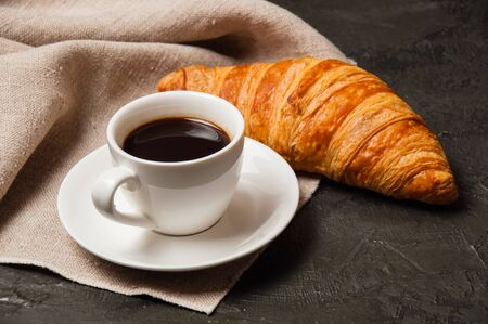 Croissant and cup of coffee and saucer on a dark background with a gray linen napkin