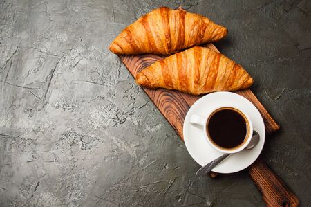 Espresso in a white cup and two croissants on a dark background, on a wooden board, place for text from the left, top view, flat lay Standard-Bild - 138725901