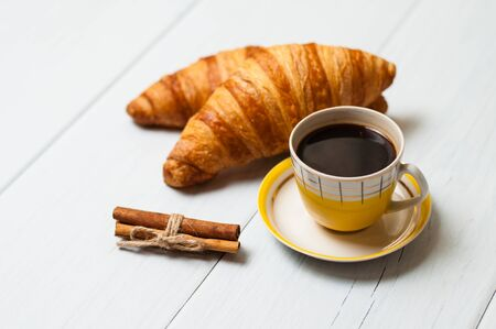 Espresso coffee in a vintage yellow cup, croissants and cinnamon on a light background, breakfast concept Standard-Bild - 138725422