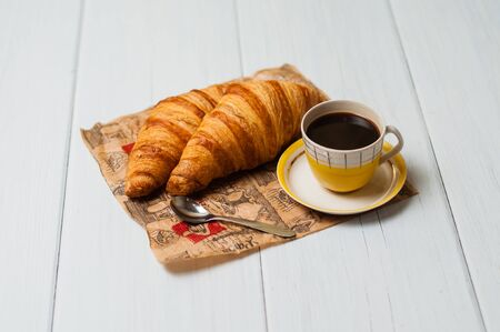 Espresso coffee in a vintage yellow cup with a saucer and spoon, croissants on craft paper, on a light background, breakfast concept Standard-Bild - 138726954