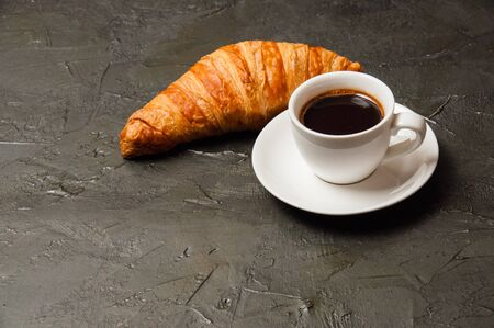 Coffee in a white cup and a croissant on a dark concrete background, view from the top, there is a place for text. Concept breakfast, coffee break or business lunch Standard-Bild - 138726955
