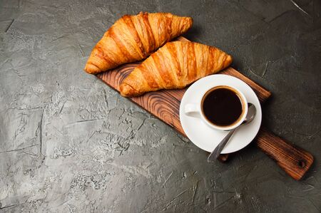 Espresso in a white cup and two croissants on a dark background, on a wooden board, place for text from the left, top view, flat lay Standard-Bild - 138726958