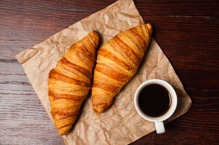 Delicious croissants and ristretto coffee in a white cup on vintage crumpled craft paper, on a dark wooden tabletop Standard-Bild - 138720985