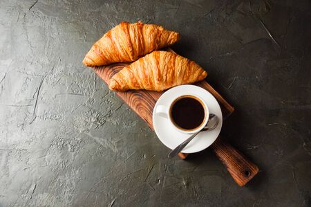 Espresso in a white cup and two croissants on a dark background, on a wooden board, place for text from the left, top view, flat lay Standard-Bild - 138726960