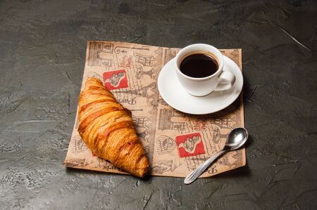 Croissant and a cup of coffee and saucer on craft paper on a dark background, vintage style, closeup, view from the top Standard-Bild - 138720699