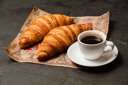 Croissants and a cup of coffee with a saucer on craft paper on a dark background, vintage style Standard-Bild - 138726962