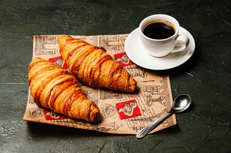 Croissant and a cup of delicious coffee and saucer on craft paper on a dark background, vintage style, close up, top view Standard-Bild - 138720625