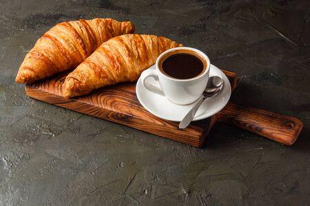 Ristretto or espresso coffee and croissants on a dark background, on a wooden board Standard-Bild - 138726965