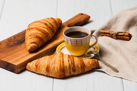 Coffee in a vintage yellow cup with a saucer, spoon and croissants with cinnamon on a wooden plate, linen napkin, on a light background, a rustic breakfast concept Standard-Bild - 138726966