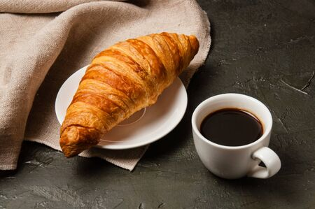 Croissant and cup of coffee with a spoon and saucer on a dark background with gray linen cloth Standard-Bild - 138726968