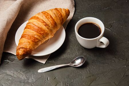 Croissant and cup of coffee with a spoon and saucer on a dark background with gray linen cloth Standard-Bild - 138726969