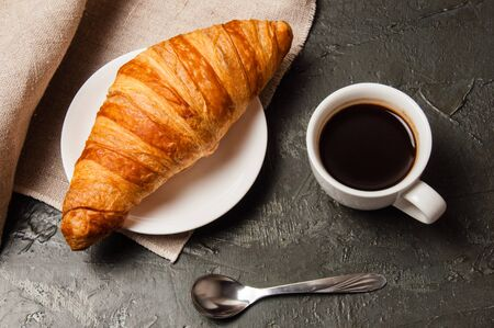 Croissant and cup of coffee with a spoon and saucer on a dark background with gray linen cloth Standard-Bild - 138726971