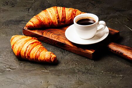 Tasty croissants and coffee in a white cup on a dark background, side view Standard-Bild - 138720917