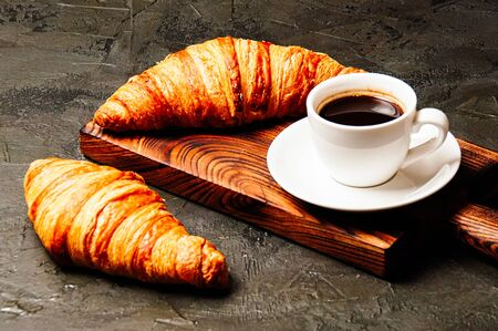 Tasty croissants and coffee in a white cup on a dark background, side view Standard-Bild - 138720547