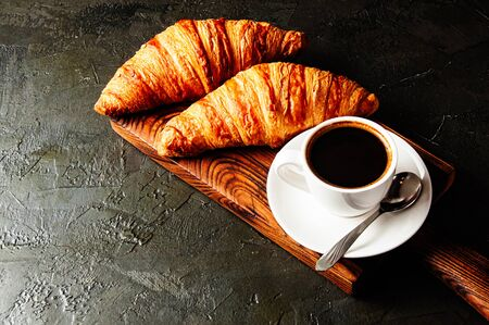 The concept of a delicious breakfast, croissants and espresso on a dark wooden board, on gray concrete, view from the top, flat lay Standard-Bild - 138720853