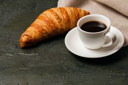 Croissant and cup of coffee and saucer on a dark background with a gray linen napkin Standard-Bild - 138726974