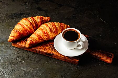 Appetizing breakfast, croissants and coffee in a white cup with a spoon and a saucer on a wooden plate, on a dark gray table under concrete Standard-Bild - 138726975