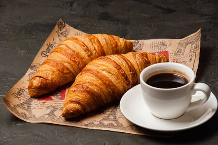 Croissants and a cup of coffee with a saucer on craft paper on a dark background, vintage style Standard-Bild - 138726976