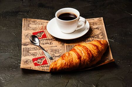 French croissant, sweet strong coffee in a white cup on a saucer with a spoon, on a beautiful craft paper, on a dark background Standard-Bild - 138721063