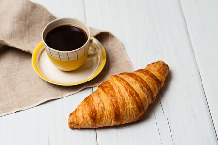 Espresso in vintage yellow cup with saucer and spoon, on linen napkin croissants on a light background, concept of lunch Standard-Bild - 138720875