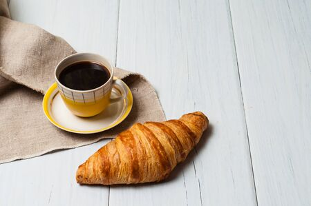 Espresso in vintage yellow cup with saucer and spoon, on linen napkin croissants on a light background, concept of lunch Standard-Bild - 138720804