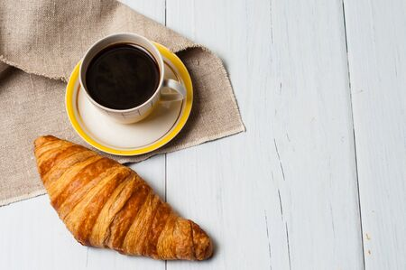 Espresso in vintage yellow cup with saucer and spoon, on linen napkin croissants on a light background, concept of lunch Standard-Bild - 138720799