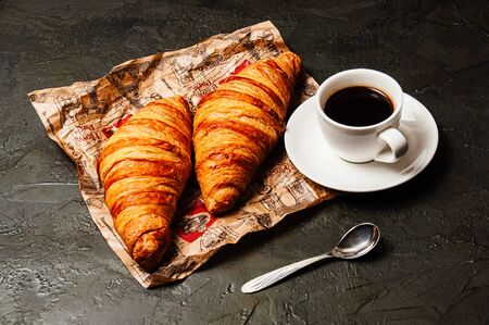 Sweet tasty croissants, a white cup of strong ristretto coffee on a saucer with a spoon on craft paper on a dark background with copy space Standard-Bild - 138720599