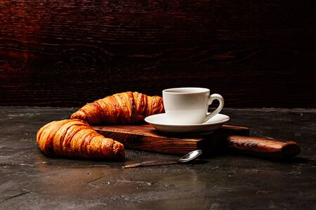 Tasty croissants and coffee in a white cup on a dark background, side view Standard-Bild - 138720764