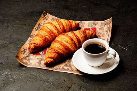 Sweet tasty croissants, a white cup of strong ristretto coffee on a saucer on craft paper on a dark background with copy space Standard-Bild - 138720811