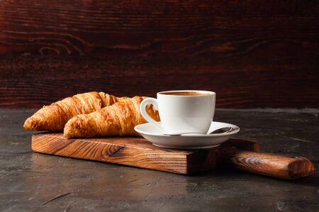 Espresso in a white cup and two croissants on a dark background, on a wooden board, place for text, side view Standard-Bild - 138726979