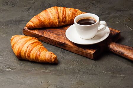 Coffee in white cup and a croissant on a dark concrete background, on a wooden board. Concept for breakfast, coffee break or business lunch. Standard-Bild - 138726987