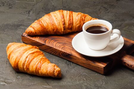 Coffee in white cup and a croissant on a dark concrete background, on a wooden board. Concept for breakfast, coffee break or business lunch. Standard-Bild - 138726988