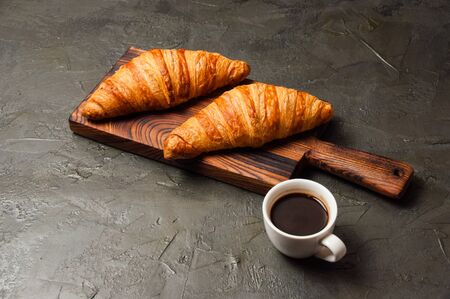 Strong espresso or ristretto coffee in a white cup and two tasty croissants on a dark concrete background, on a wooden board, flat lay. Concept for breakfast, coffee break or business lunch. Standard-Bild - 138726989
