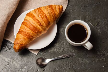 Croissant and cup of coffee with a spoon and saucer on a dark background with gray linen cloth Standard-Bild - 138726990