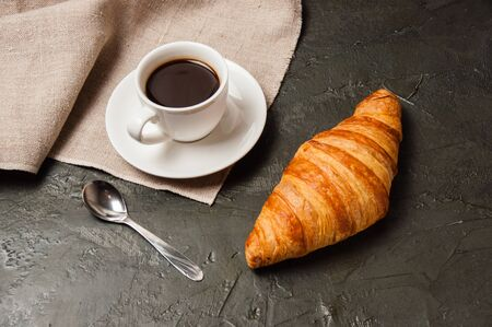 Croissant and cup of coffee with a spoon and saucer on a dark background with gray linen cloth Standard-Bild - 138726991