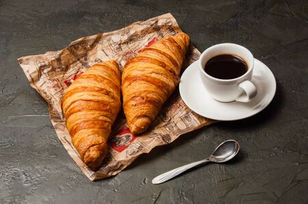 Delicious croissants on crumpled craft paper and espresso in a white cup with a spoon on a dark gray background, vintage style Standard-Bild - 138720808