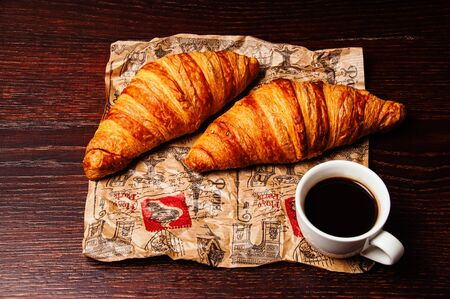 Delicious croissants and coffee in a white cup on vintage crumpled craft paper, on a dark wooden tabletop Standard-Bild - 138720682