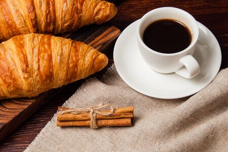 Concept delicious breakfast. Cinnamon croissants, a cup of coffee and a linen napkin on a wooden table, top view, flat lay Standard-Bild - 138720733