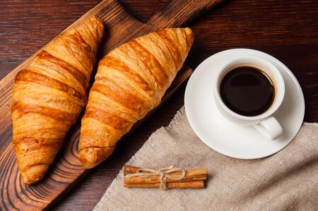 Concept delicious breakfast. Cinnamon croissants, a cup of coffee and a linen napkin on a wooden table, top view, flat lay Standard-Bild - 138720824