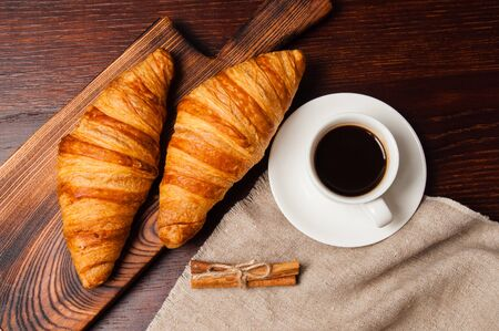 Concept delicious breakfast. Cinnamon croissants, a cup of coffee and a linen napkin on a wooden table, top view, flat lay Standard-Bild - 138720965